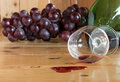 Red wine spilled and grapes fruit from glass green bottle Royalty Free Stock Images