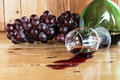 Red wine spilled and grapes fruit from glass green bottle Stock Image