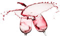 Red wine splashes from two glasses isolated on the white backgro Royalty Free Stock Photo