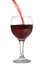 Red wine stream of flows in a wineglass isolated on white Stock Photos