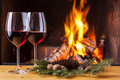 Red wine for two at fireplace decorated christmas Stock Photo
