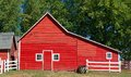 Red wisconsin barn with door and three windows a single small sits on a farm in rural Royalty Free Stock Photo