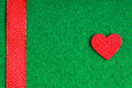 Red wooden decorative heart on green cloth background valentine s day love symbol textile with ribbon blank copy space Royalty Free Stock Photo