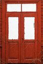 Red wooden door closed with white windows Stock Photo