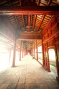 Red wooden hall of hue citadel in vietnam asia beautiful with golden ornate details vanishing roof and tiled floor sunlight Royalty Free Stock Image
