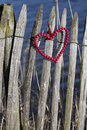 Red wooden heart on a fence of beads hanging Royalty Free Stock Images