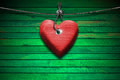 Red wooden heart on green wood background handmade hanging a steel cable Royalty Free Stock Images