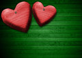 Red wooden hearts on green wood background two handmade hanging Stock Images
