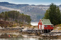 Red wooden house on the coast in norway stands sea Stock Photography