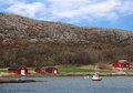 Red wooden houses on rocky coast traditional small norwegian village with and small fishing boat nearby Royalty Free Stock Photo