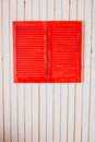 Red wooden shutters on a white wall of the house Stock Photo
