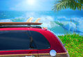 Red woody car with surfboard at beach w big waves Royalty Free Stock Photo