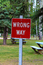 A red wrong way sign with picnic tables behind it Royalty Free Stock Photo