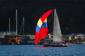 Red yellow blue spinaker sailboat a with a passes houseboats during a race in seattle washington Royalty Free Stock Photos