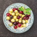 Red and yellow cherries in dark ceramic bowls on a dark background. Top view Royalty Free Stock Photo