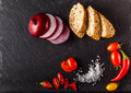 Red and yellow cherry tomatoes on slate with sliced bread, onion Royalty Free Stock Photo