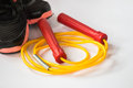 Red and yellow color jump rope with sport shoe Royalty Free Stock Photo