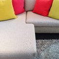 Red and yellow cushions on gray corner sofa