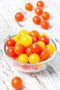 Red and yellow fresh cherry tomatoes in glass bowl with water drops a on a wooden table Stock Photography