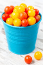 Red and yellow fresh cherry tomatoes with water drops in bowl a blue bucket on a wooden table Stock Image