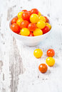 Red and yellow fresh cherry tomatoes in white bowl with water drops on wooden table Royalty Free Stock Photography