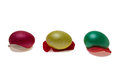 Red yellow green easter eggs top rose petals isolated against white background Stock Images