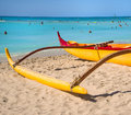 Red yellow outrigger canoe sits sand waikki beach turquoise blue water pacific ocean background filled people enjoying their Stock Images