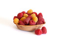Red and yellow raspberries in the wooden plate on white background Royalty Free Stock Image