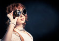 Redhair steampunk woman with goggles beautiful looking over her aside on the dark backgroud Royalty Free Stock Photography