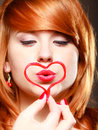 Redhaired girl holding red heart love blowing kiss valentines day happy symbol young woman studio shot Stock Images