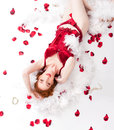 Redhaired woman wearing red lingerie with rose petals and white feather boa Royalty Free Stock Photos