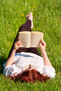 Redhead beautiful girl reading a book in nature Royalty Free Stock Image