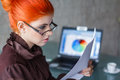 Redhead businesswoman with glasses reading document at office Stock Photo