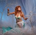 Redhead elf woman with a lantern in magical forest Stock Photos