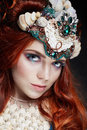 Redhead girl with bright makeup and big lashes. Mysterious fairy woman with red hair. Big eyes and colored shadows, long lashes