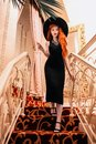 Redhead girl in classic dress on stairs. Noir film. Luxury vintage woman. Lady in classic retro hat. Redhead woman in restaurant.