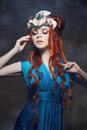 Redhead girl fabulous look, blue long dress, bright makeup and big eyelashes. Mysterious fairy woman with red hair. Big eyes