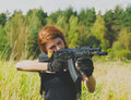 Redhead girl with a gun in his hand Royalty Free Stock Photo