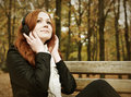 Redhead girl with headphones listen music on player in city park, fall season Royalty Free Stock Photo