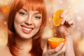 Redhead girl holding orange on bokeh background Royalty Free Stock Photos