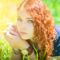 Redhead girl lay on grass beautiful soft focus eyes with green highlights the face Royalty Free Stock Photo