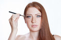 Redhead girl with a makeup brush near her eye Royalty Free Stock Photo