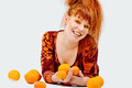 Redhead girl with oranges happy Stock Image