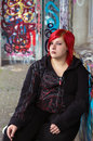 Redhead girl with piercing on graffiti background beauty and lonely sitting in front of wall outdoors Royalty Free Stock Photos
