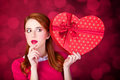 Redhead girl with shape heart box photo red background bokeh Royalty Free Stock Images