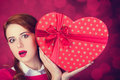 Redhead girl with shape heart box photo red background bokeh Royalty Free Stock Photo