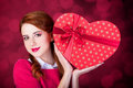Redhead girl with shape heart box photo red background bokeh Royalty Free Stock Photos