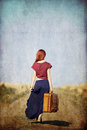 Redhead girl with suitcase at countryside road Royalty Free Stock Photo