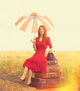 Redhead girl with suitcases and umbrella at outdoor nar wheat field Stock Photo