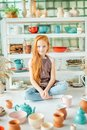 Girl wih many cups made from clay sitting in pottery studio Royalty Free Stock Photo